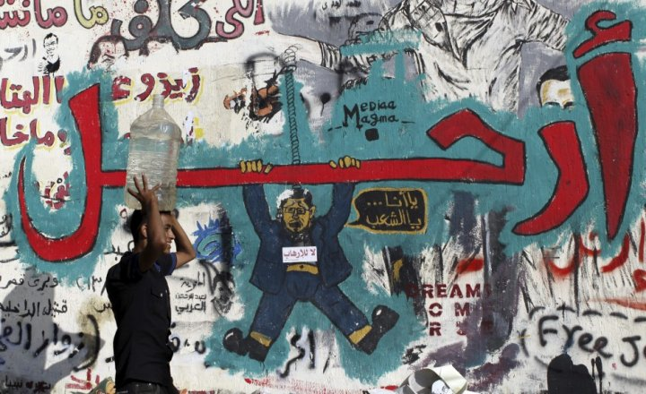 "Graffiti artwork by the anti-MB campaign depicting Morsi dangling from the word ""Leave."" In the artwork, Morsi is saying, ""Either me…or the people."" (Photo credit: Reuters)"