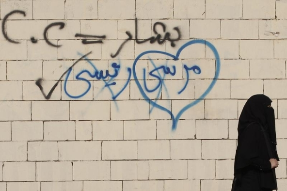 "On top, a spray-painted slogan saying, ""Bashar [Syrian President] = C.C [Egyptian President]."" On the bottom side of the concrete is an opposing spray-painted phrase stating, ""Morsi is my president."" (Photo credit: Reuters-Amr Abdullah Dalsh)"