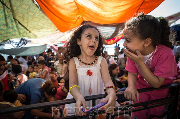 "Two Egyptian girls play during a gathering at a church as they celebrate the traditional festival ""Sham el-Nessim"" in 2014. Credit: Pan Chaoyue"