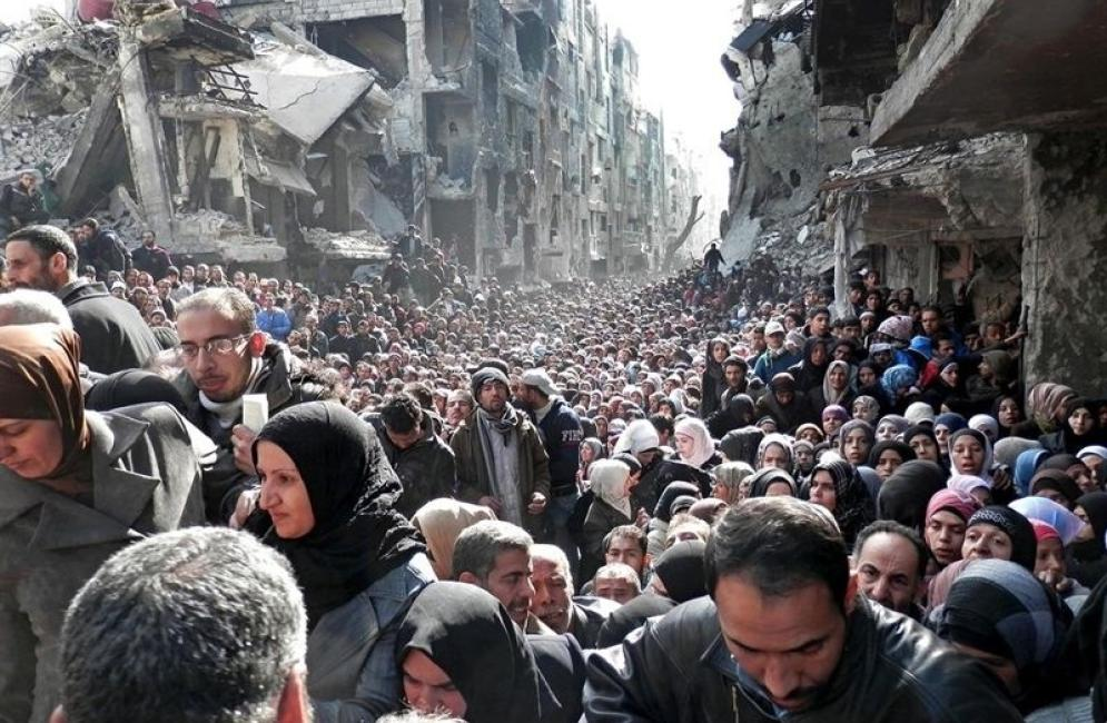 Refugees in Yarmouk wait to receive food from UNRWA in 2014.