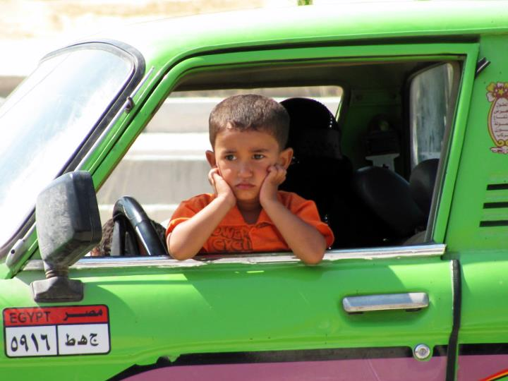 A child waiting for his father in a pickup truck to return from the market, North Coast