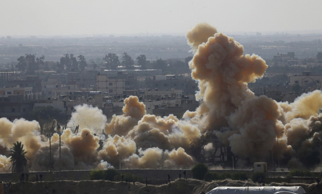 Smoke rises as a house is blown up during a military operation by Egyptian security forces in the Egyptian city of Rafah, near the border with southern Gaza Strip November 3, 2014. Egypt began clearing residents from its border with the Gaza Strip last week to create a buffer zone following some of the worst anti-state violence since President Mohamed Mursi was overthrown last year. REUTERS/Ibraheem Abu Mustafa (GAZA - Tags: POLITICS CIVIL UNREST)