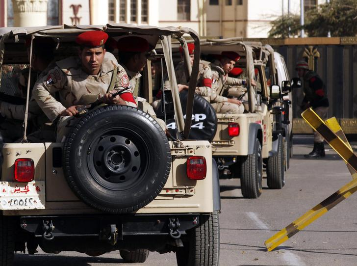 Soldiers in a convoy secure a military funeral ceremony of security personnel killed in attacks in Sinai, outside Almaza military airbase where the funerals were held, in Cairo