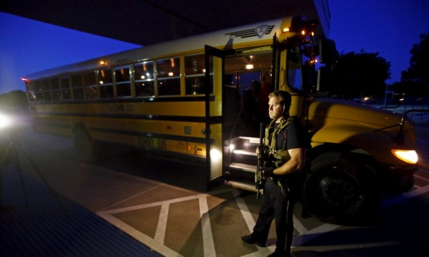 A police officer stands by a school bus used to evacuate attendees of the event under attack