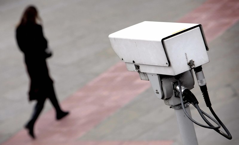 A police CCTV camera observes a bypassing woman. Credit: Leon Neal/AFP