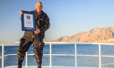 Gabr holding the Guinness World Record certificate for the deepest scuba dive