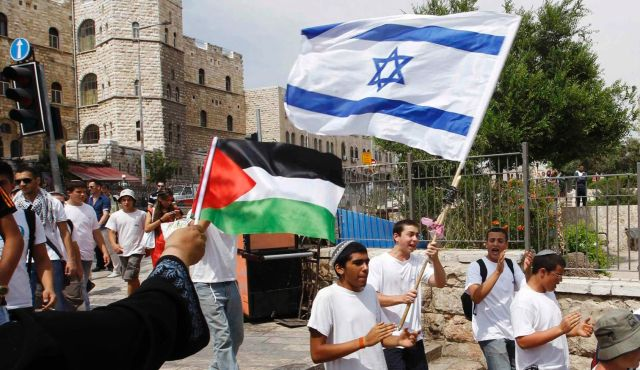 Woman waves Palestinian flag as Israeli youths with Israeli flag walk by in Jerusalem. Credit:  Reuters