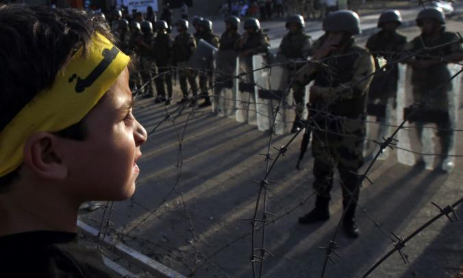 "A boy, his headband inscribed with the word ""Rabaa,"" faces soldiers and riot police near Rabaa al Adawiya Square, which was home to the pro-Morsi sit-ins in 2013.  Credit: Amr Abdallah Dalsh/ Reuters"