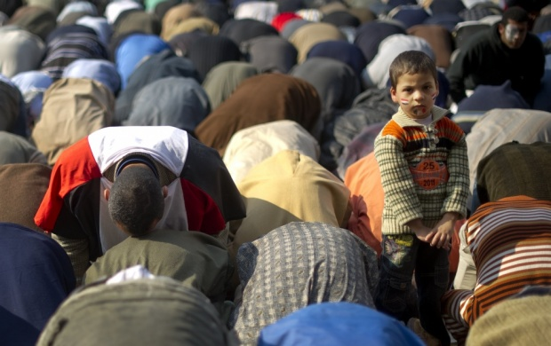 A young boy stands as anti-military rule protestors pray before a demonstration at Tahrir square in Cairo. Credit: AFP