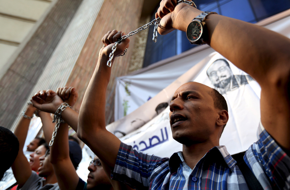 A protester holds up his hands, which are chained together, as journalists and activists protest against the restriction of press freedom and demand the release of detained journalists in front of the Press Syndicate in Cairo June 10, 2015 (Photo: Reuters)