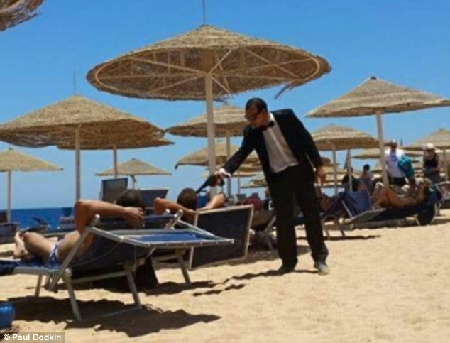 Entertainer at a Red Sea resort pointing a fake gun at British tourist days after the Sousse attack in Tunisia. Credit: Paul Dodkin