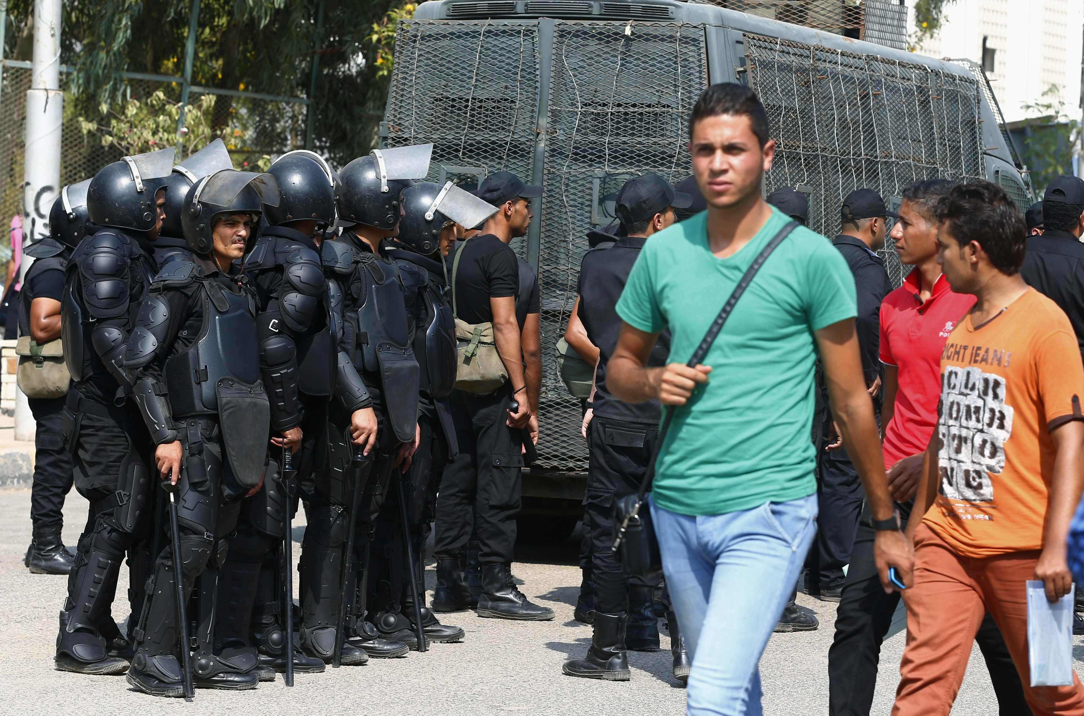 Al-Azhar University students walk past riot police during a protest conducted by the pro-Muslim Brotherhood student movement,  Students Against the Coup, October 12, 2014. Credit: Amr Abdallah Dalsh/Reuters