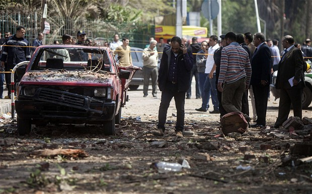 Egyptians inspect the damage after twin bombs struck police posts near Cairo University in April 2014. Credit: AFP