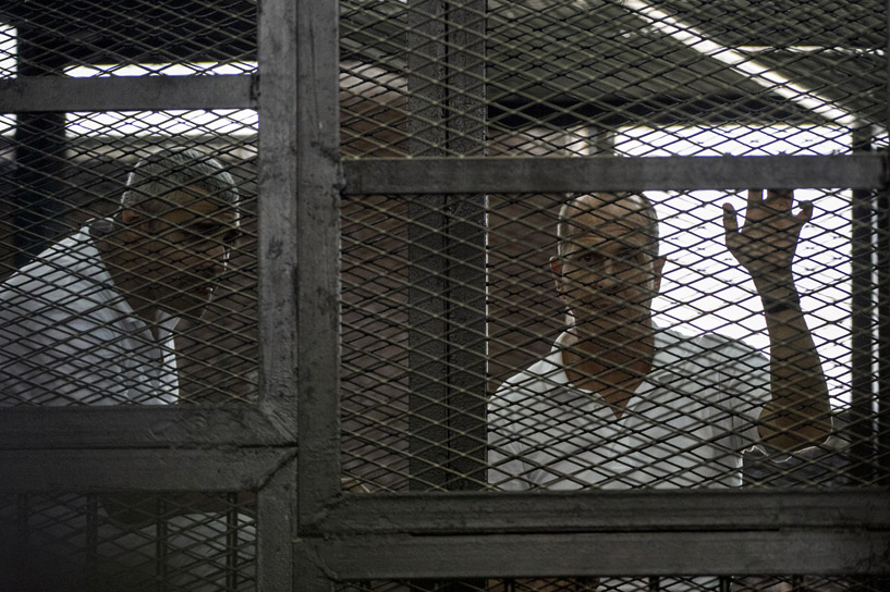 Mohamed Fahmy and Peter Greste listen to the verdict inside the defendants cage. Credit: Khaled Desouki/ AFP