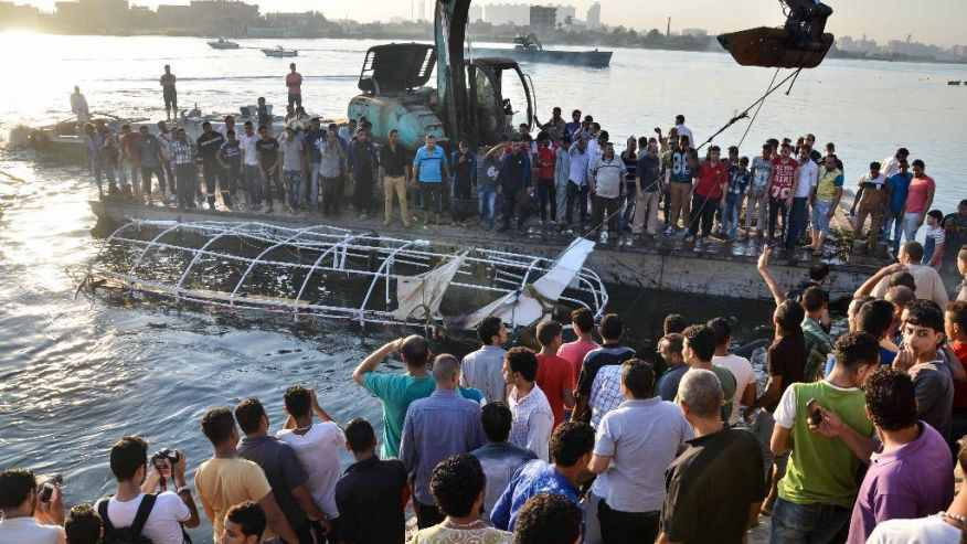 Egyptians look at the passenger boat that sunk in the river Nile in Giza, south of Cairo, Egypt, Thursday, July 23, 2015.  (AP Photo/Samer Abdullah)