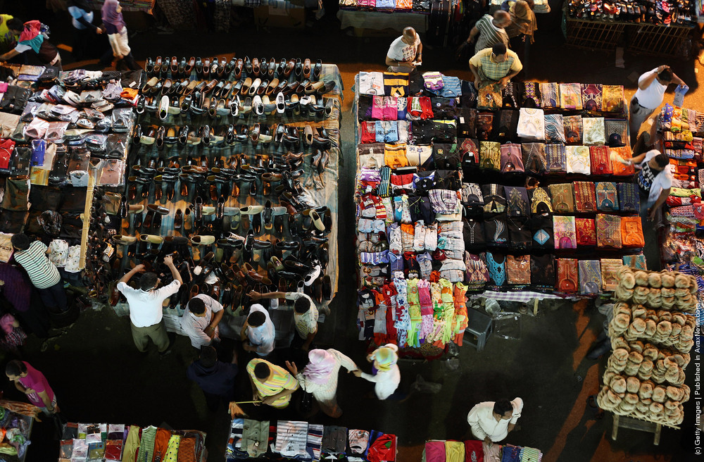 Shoppers move among tables containing clothes and shoes at Ataba market  in Cairo, Egypt. Credit: Peter Macdiarmid/ Getty Images