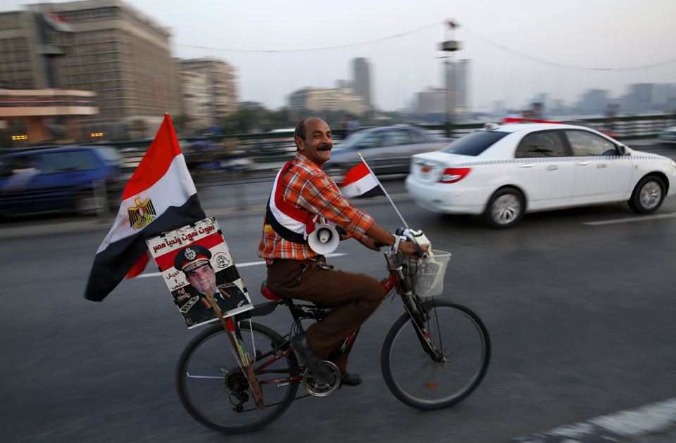 A supporter of Egyptian President Abdel-Fattah El-Sisi carries his poster on his bike as he celebrates with others for Thursday's opening of the new Suez Canal, riding on the Qasr El Nile Bridge in Cairo, Egypt, Wednesday, Aug. 5, 2015 (AP)