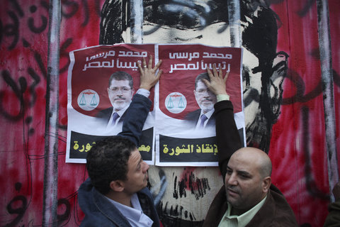 Two individuals attempting to conceal the anti-MB artwork in the background by pasting posters of Morsi. (Photo credit: Tara Todras-Whitehill for The New York Times)