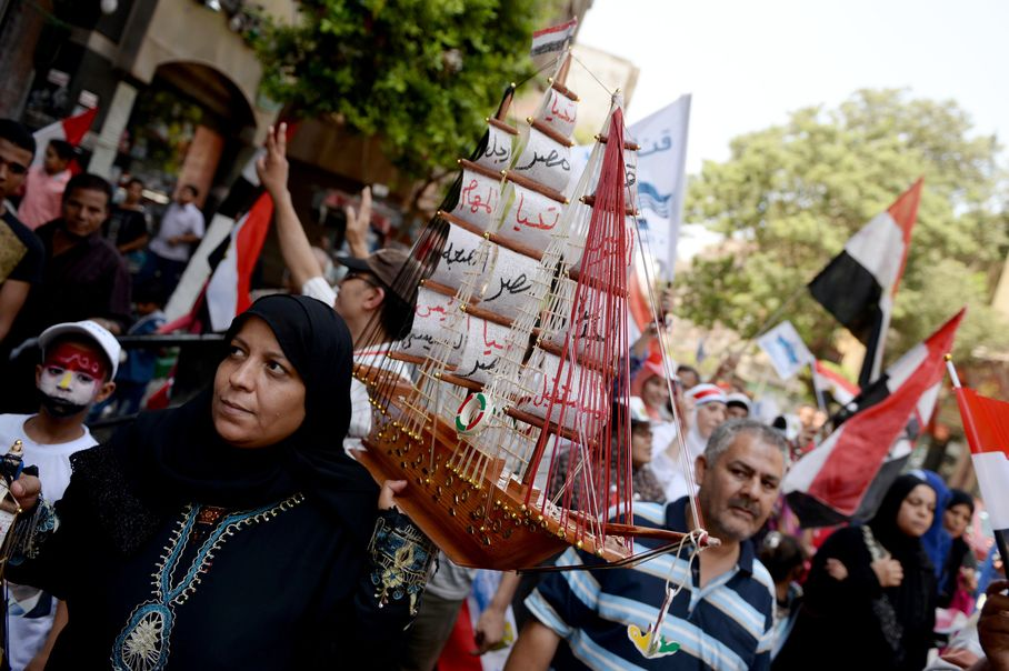 An Egyptian woman holds a small boat as she and other Egyptian's celebrate the new Suez Canal opening in Tahrir square in Cario, Egypt, Thursday, Aug. 6, 2015. Credit: Mohamed Hossam/ AP