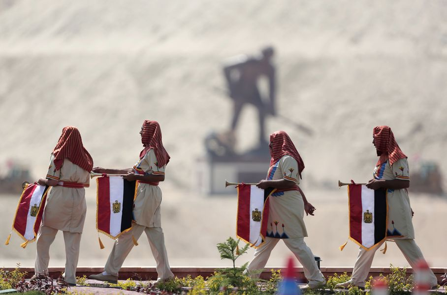 Egyptians wear Pharaonic costumes as they march in front of a statue representing a man digging the new section of the Suez Canal in Ismailia, Egypt, Thursday, Aug. 6, 2015. Credit: Hassan Ammar/ AP