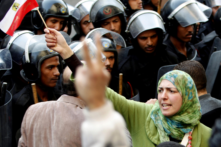 A woman holds an Egyptian flag in front of riot police during a protest in Cairo January 26, 2011.  Credit: Asmaa Waguih/ Reuters