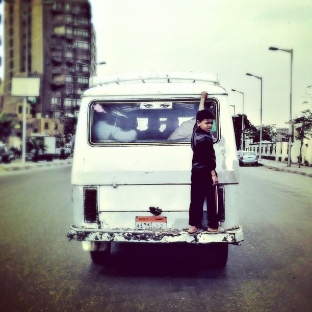 A child simply hanging off the back of a micro-bus in Giza. Photo by Roger Anis