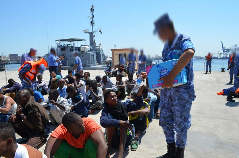 Navy officers appear to be handing out water bottles to the refugees [Credit: Military Spokesman]