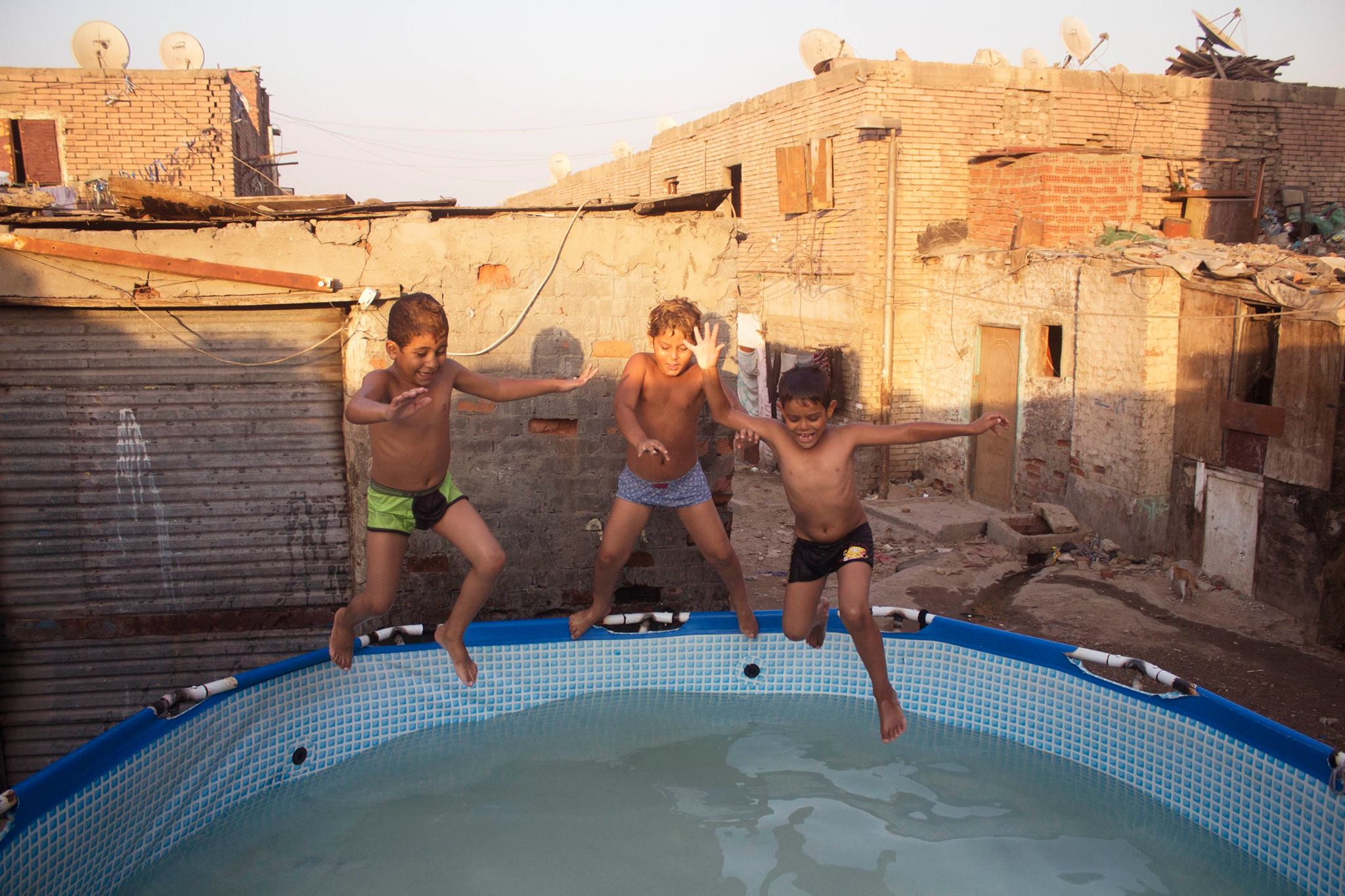 Children jumping in a 'public swimming pool' in Dwayka, Cairo.  Credit: Mostafa Darwish