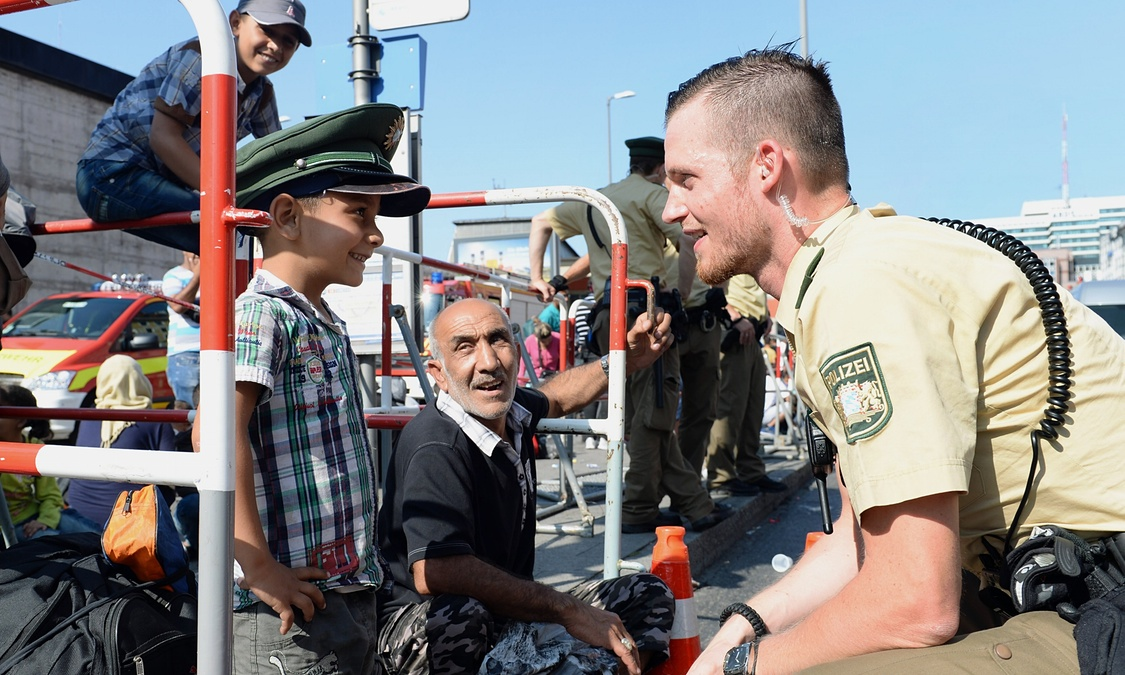 A German police officer talks to a young refugee as he waits for a bus outside the central railway station in Munich. Photograph: Christof Stache/AFP/Getty Images