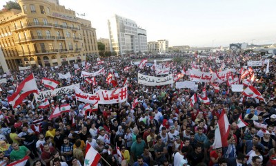 """People carry Lebanese national flags and chant slogans as they take part in an anti-government protest at Martyrs' Square in downtown Beirut, Lebanon August 29, 2015. Thousands of protesters waving Lebanese flags and chanting """"revolution"""" took to the streets of Beirut on Saturday for an unprecedented mobilisation against sectarian politicians they say are incompetent and corrupt. REUTERS/Mohamed Azakir - RTX1Q7O2"""