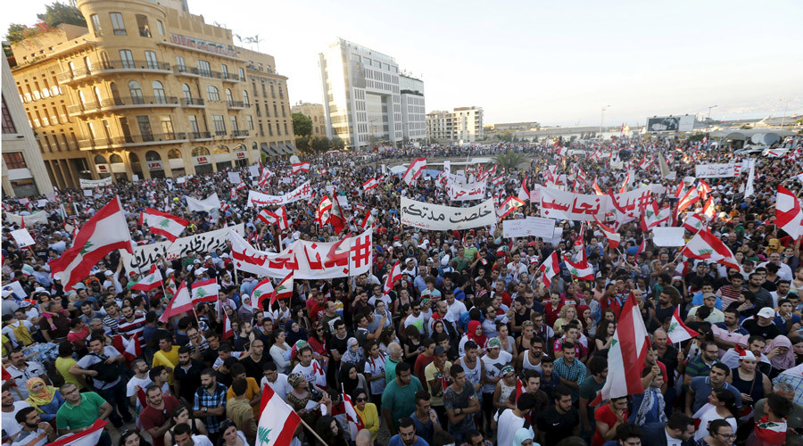 "People carry Lebanese national flags and chant slogans as they take part in an anti-government protest at Martyrs' Square in downtown Beirut, Lebanon August 29, 2015. Thousands of protesters waving Lebanese flags and chanting ""revolution"" took to the streets of Beirut on Saturday for an unprecedented mobilisation against sectarian politicians they say are incompetent and corrupt. REUTERS/Mohamed Azakir - RTX1Q7O2"
