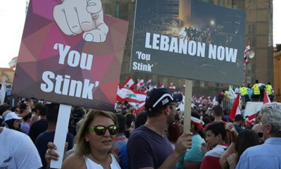 Lebanese anti-government protesters hold placards during a demonstration in Martyrs' Square, downtown Beirut, Lebanon. Credit: AP