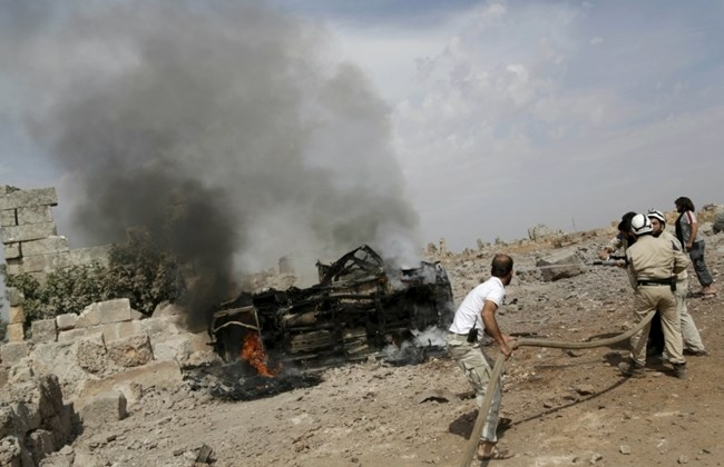 Civil defense members put out the flames on a burning military vehicle at a base controlled by rebel fighters from the Ahrar al-Sham Movement, that was targeted by what activists said were Russian airstrikes at Hass ancient cemeteries in the southern countryside of Idlib, Syria October 1, 2015. REUTERS/Khalil Ashawi