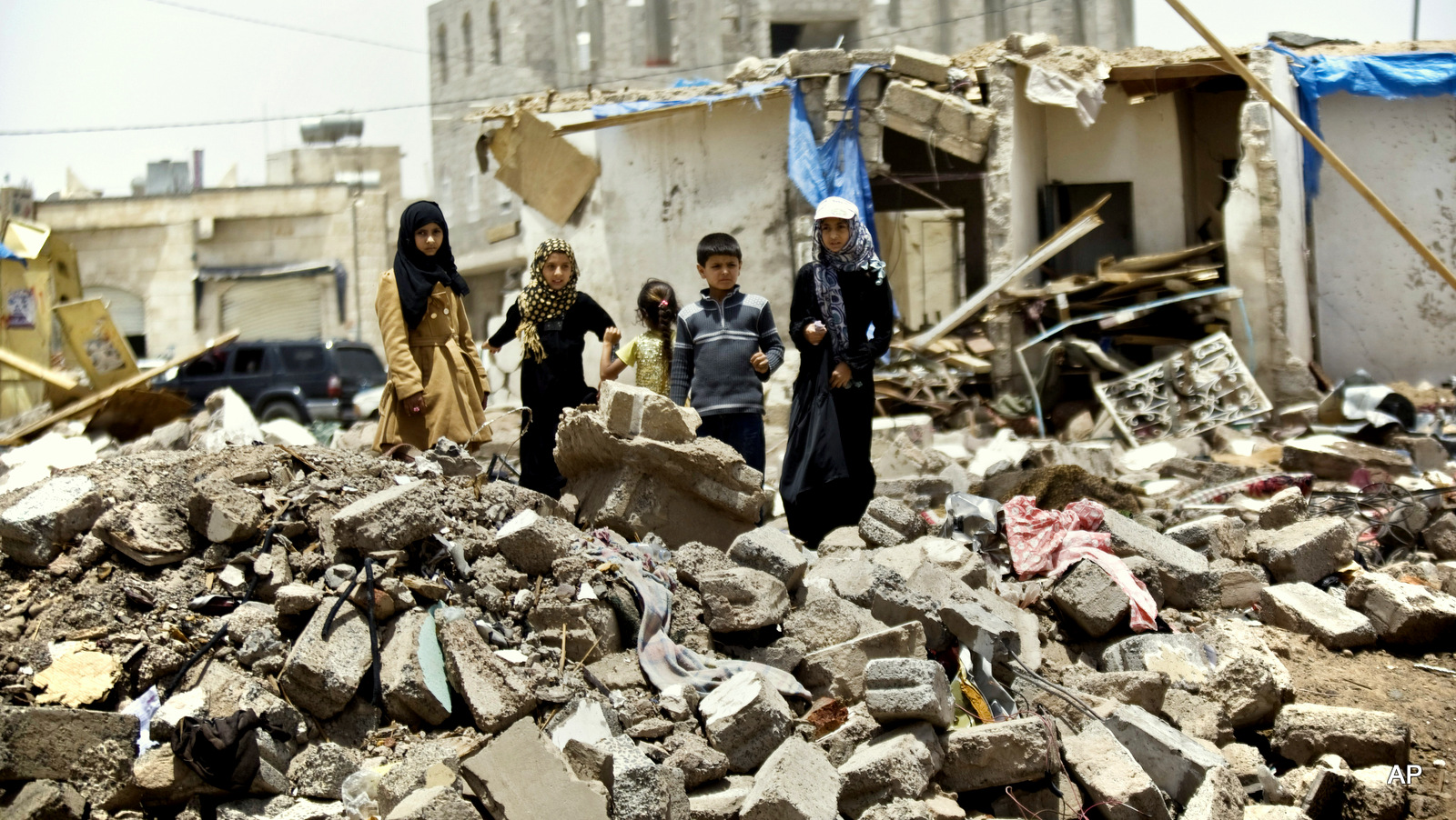 A boy and his sisters watch graffiti artists spray on a wall, commemorating the victims who were killed in Saudi-led coalition airstrikes in Sanaa, Yemen, Monday, May 18, 2015. Saudi-led airstrikes targeting Yemen's Shiite rebels resumed early on Monday in the southern port city of Aden after a five-day truce expired amid talks on the war-torn country's future that were boycotted by the rebels. (AP Photo/Hani Mohammed)