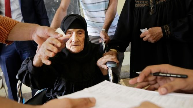 An elderly woman votes in Giza