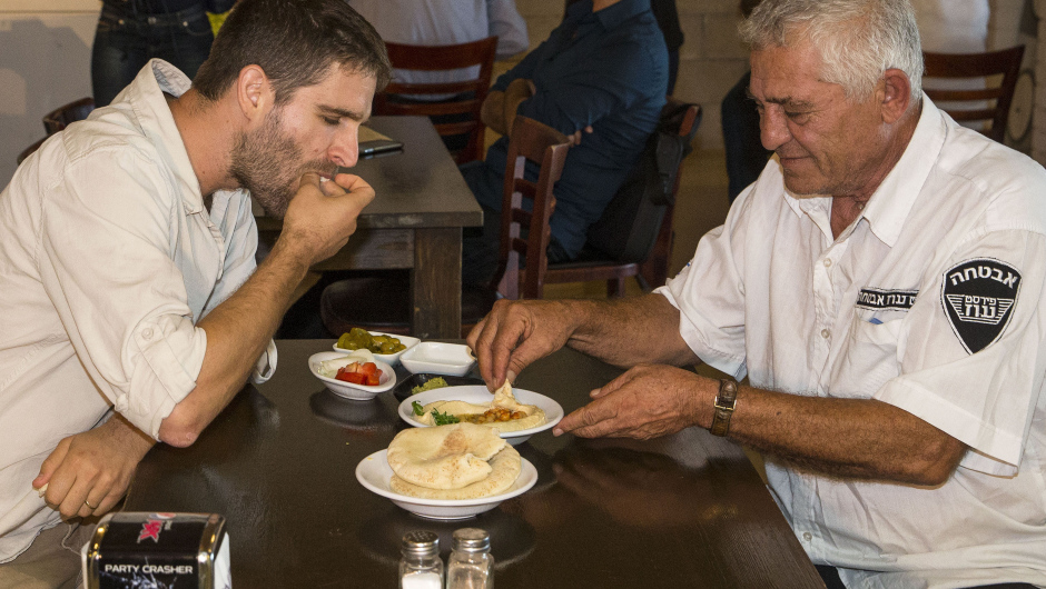 Israeli Jew David (L), 31, and Muslim Arab-Israeli Mahmoud, 62, share a plate of hummus at the Hummus bar. Photo: JACK GUEZ/AFP/Getty Images)