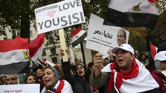 A supporter (C) welcoming the expected visit of Egyptian President Abdel Fattah el-Sissi holds a placard as other supporters wave Egyptian flags outside Downing Street in central London on November 5, 2015. (AFP PHOTO / JUSTIN TALLIS)