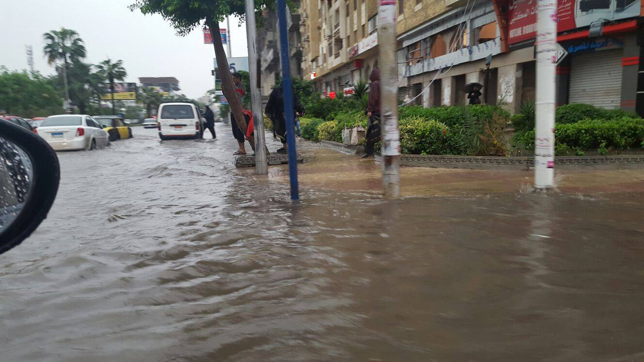 Alexandrian citizens try to find high ground as the rainwater floods the streets and pours over the sidewalks. Photo: Reem Sami Abul Enain