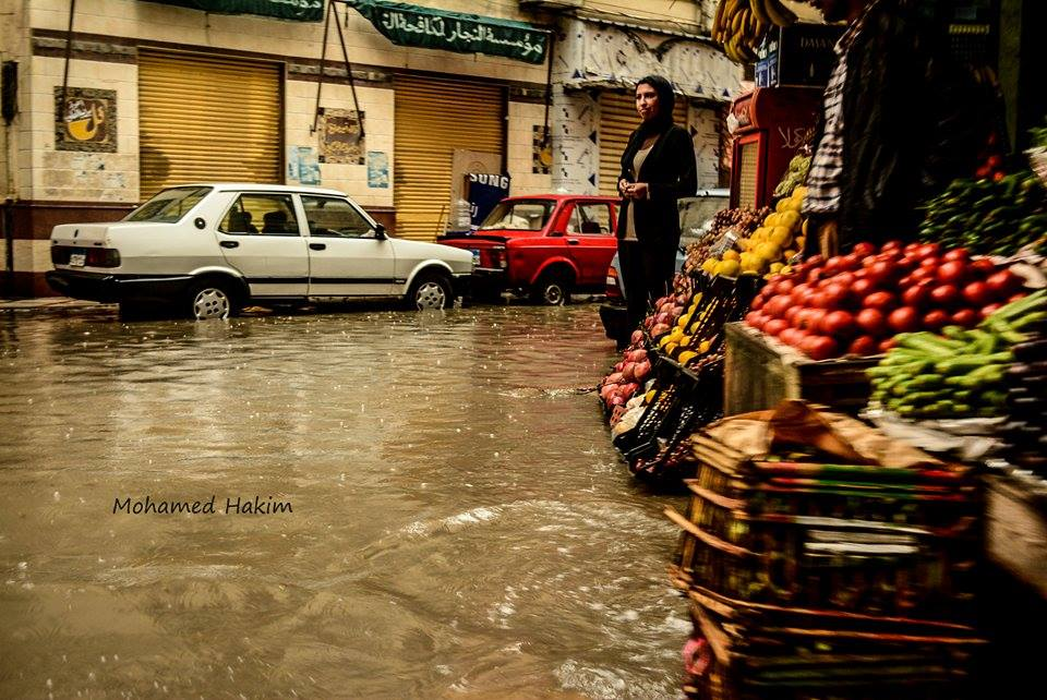 A woman stands on the sidewalk in front of a fruit and vegetable shop, with the rainwater flooding the streets reaching the shop's entrance. Photo: Mohamed Hakim