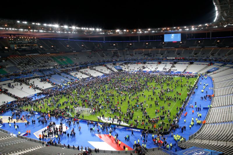 Football fans gather on the Stade de France field after evacuation orders following two suicide bombs that detonated as part of a the 'Friday Paris attacks'.