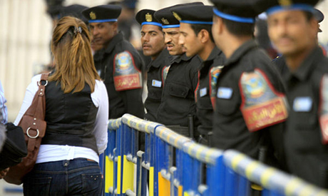Policemen keeping guard of a facility near the Nile glare at a woman as she passes by. Credit: AP