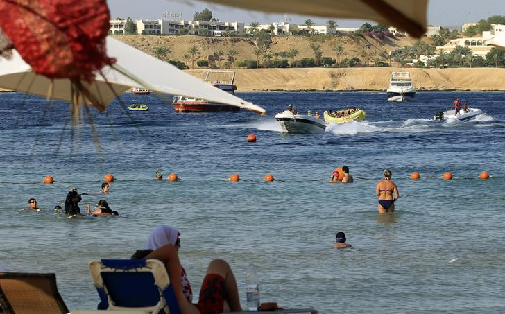 People enjoy the beach at the Red Sea resort of Sharm el-Sheikh in the South Sinai governorate, about 550 km (342 miles) south of Cairo, July 12, 2012. Egypt expects to receive more than 12 million tourists by the end of 2012, a 23 percent rise over the previous year, the tourism minister said on July 17, 2012, adding that he did not expect the election of a new Islamist president to stifle the industry. Picture taken July 12. REUTERS/Amr Abdallah Dalsh  (EGYPT - Tags: SOCIETY TRAVEL BUSINESS)