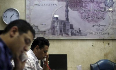 Employees speak on phones at an exchange office in downtown Cairo June 5, 2014. REUTERS/Amr Abdallah Dalsh