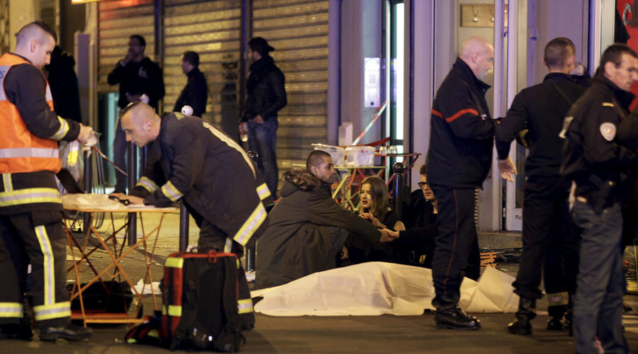 A general view of the scene that shows rescue services personnel working near the covered bodies outside a restaurant following a shooting incident in Paris, France, November 13, 2015. REUTERS/Philippe Wojazer