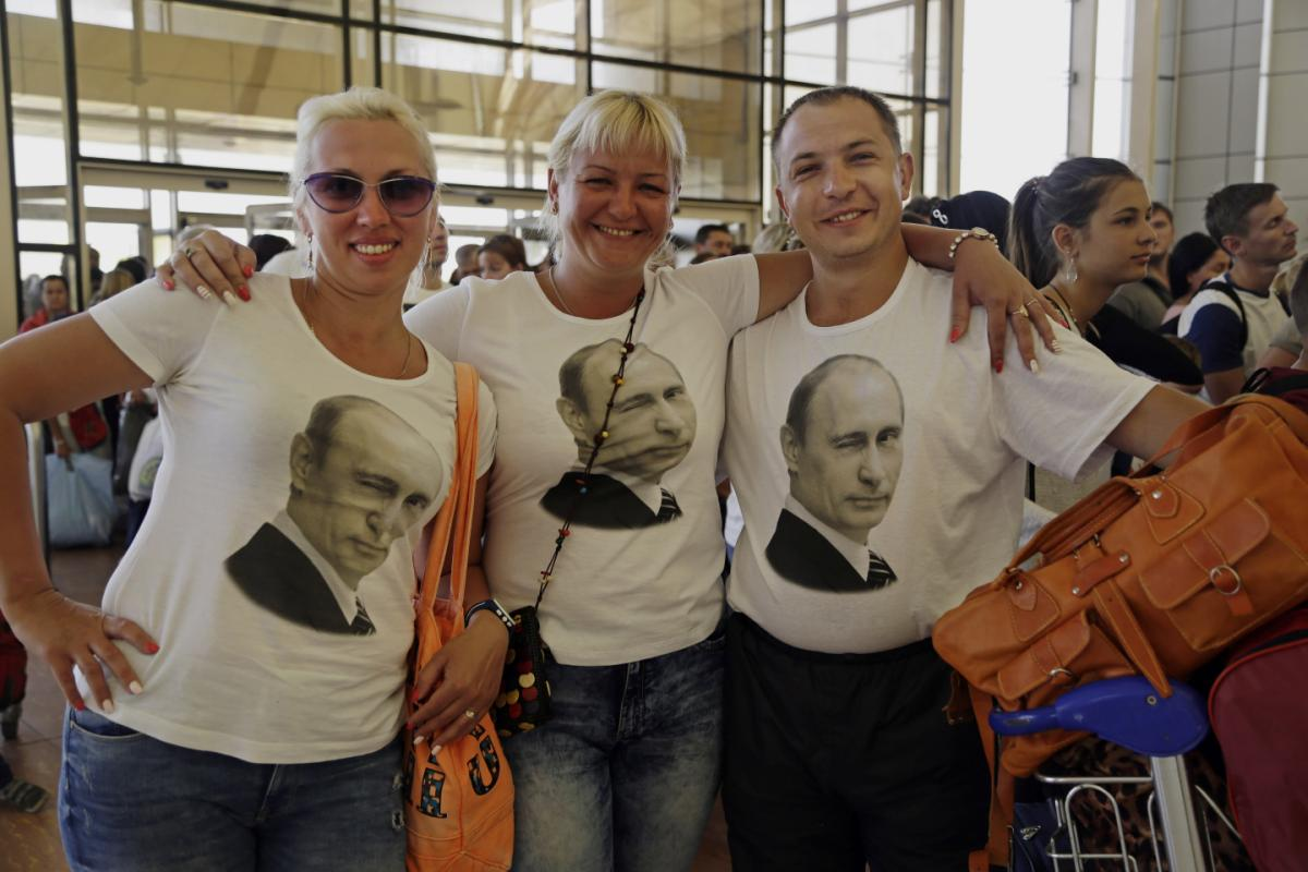Russian tourists wearing t-shirts with images of Russian President Vladimir Putin pose for a photo in the departure terminal before boarding a flight from Sharm el-Sheikh (AP/Thomas Hartwell)