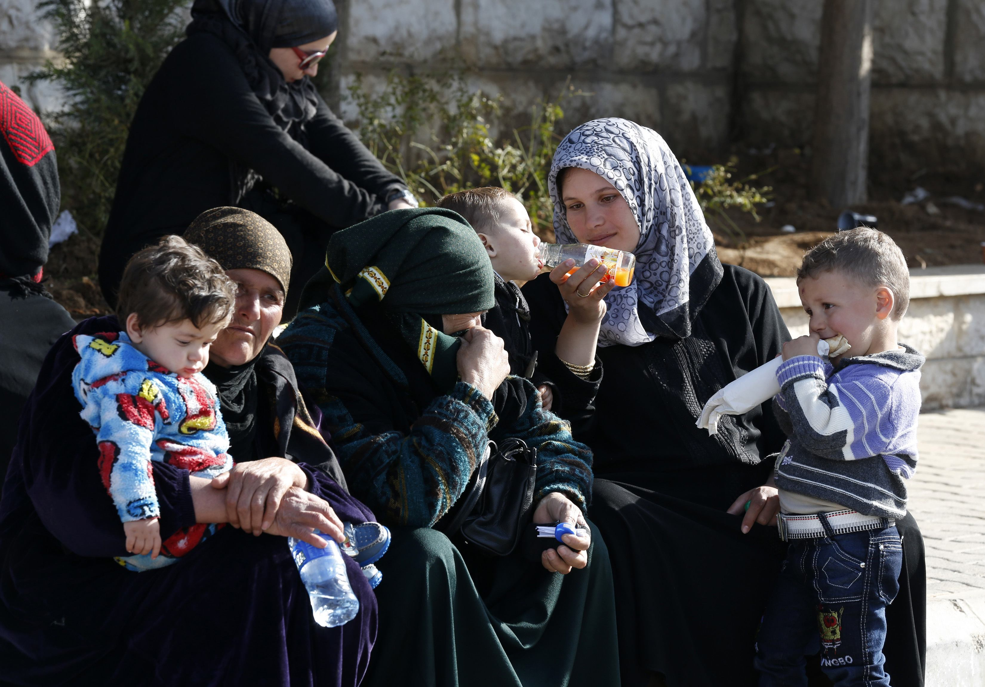 Syria women and children wait to get a visa stamp to enter Lebanon. Credit: Jamal Saidi/ Reuters