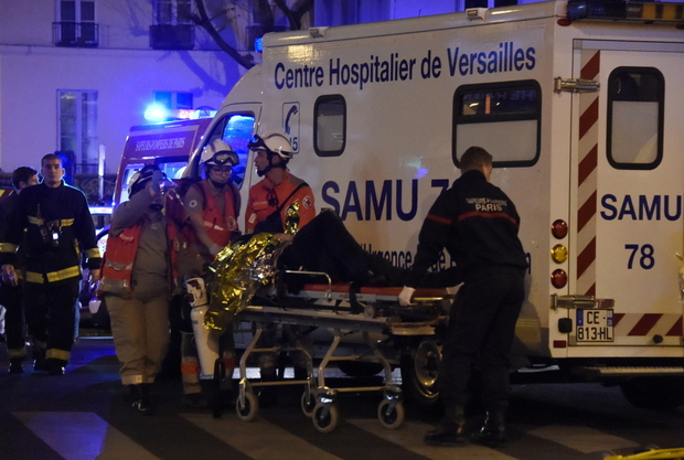 Firefighters and rescuers evacuate an injured person near the Bataclan concert hall in central Paris, on November 14, 2015. Photo: Dominique Faget, AFP