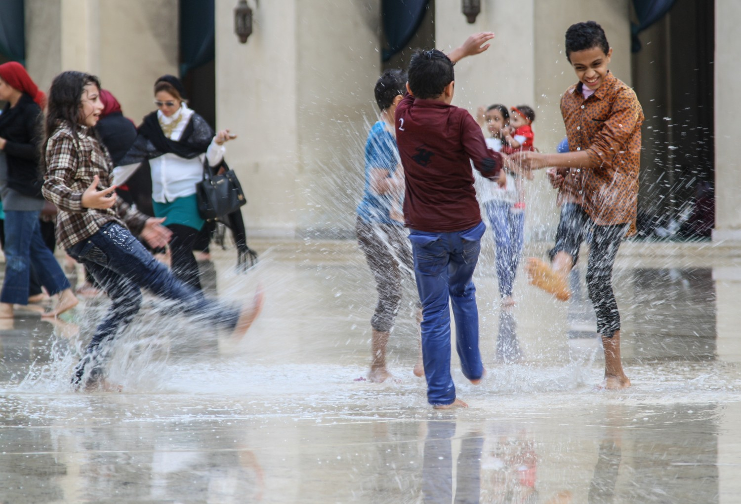Children splashing water in the vast hall of al-Hakim mosque in Cairo after heavy rains. Credit: Enas El Masry