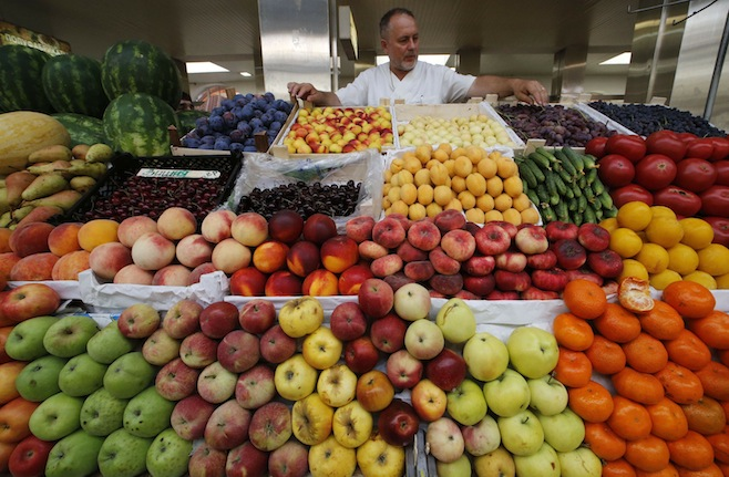 A vendor sells vegetables and fruits at the city market in St.Petersburg, Russia. PHOTO: Alexander Demianchuk/Reuters