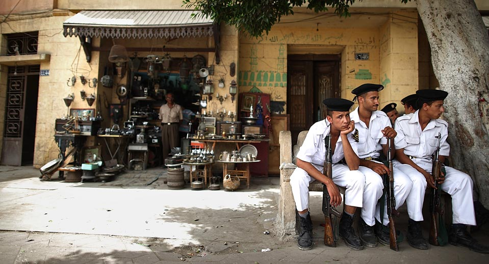 Tourist Police sit in the shade on a road leading to the Coptic Cairo area. Credit: Peter Macdiarmid/ Getty